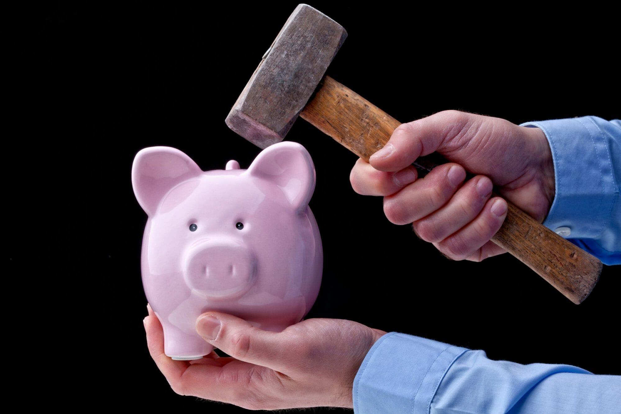 Businessman-smashing-a-piggy-bank-765241-scaled