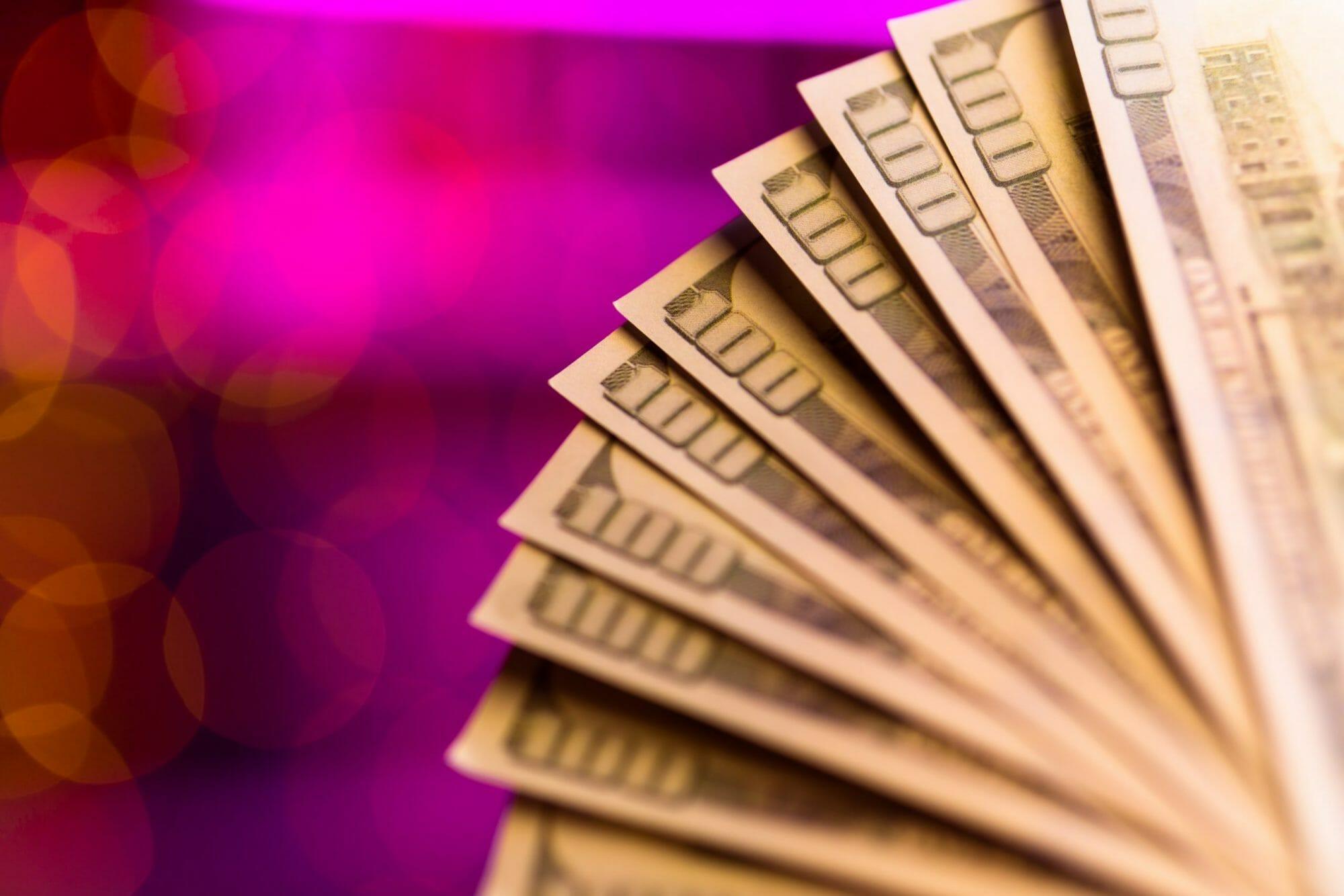 Many-dollar-bills-on-pink-background-965596-scaled